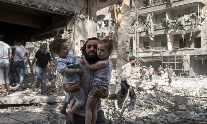 A Syrian man carries his two girls as he walks across the rubble following a barrel bomb attack on the rebel-held neighborhood of al-Kalasa in the northern Syrian city of Aleppo on Sept. 17. The Chinese regime is supplying weapons to the Assad regime, through Iran.  (Karam al-Masri/AFP/Getty Images)