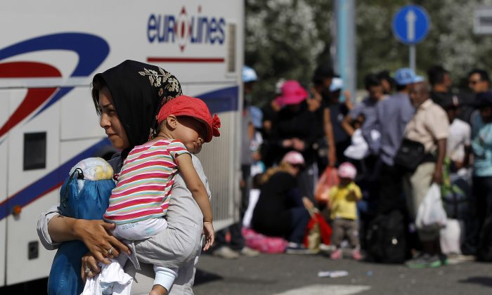 Migrants board a bus which will take them to Croatia at the Horgos border crossing with Hungary on September 17, 2015 in Horgos, Serbia. (Srdjan Stevanovic/Getty Images)