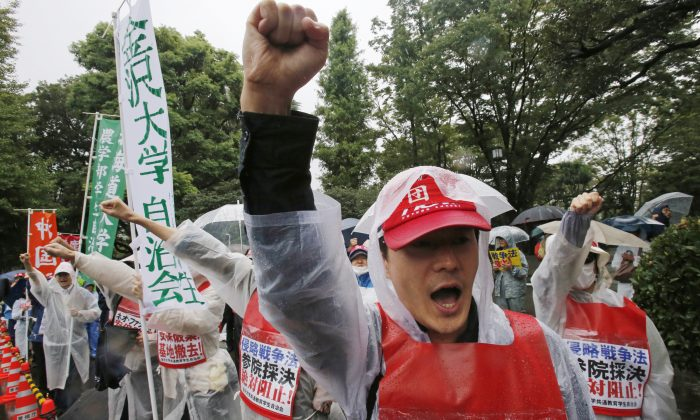 Protesters shout an anti-security bills slogan during a rally in rains in front of the Parliament building in Tokyo Thursday, Sept. 17, 2015.  (AP Photo/Shuji Kajiyama)