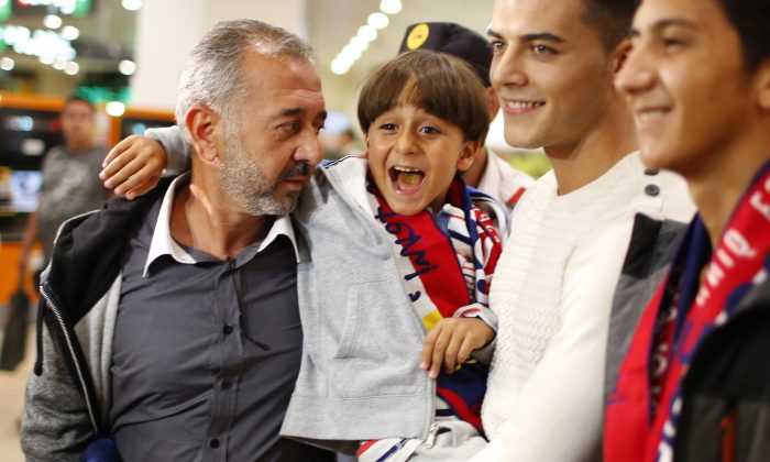 Syrian Osama Abdul Mohsen, left, holds his son Zaid as they arrive at the Barcelona train station on Wednesday, Sept.16, 2015. (AP Photo/Manu Fernandez)