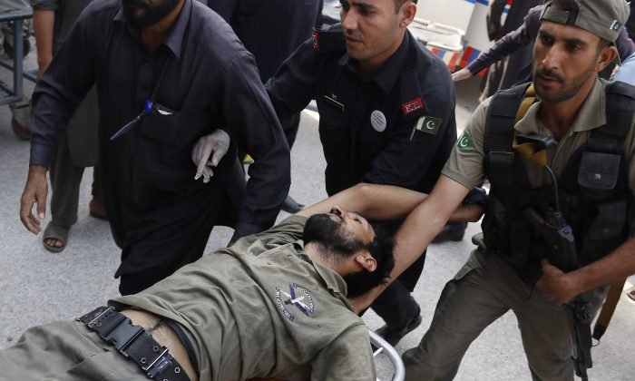 Pakistani security officials rush their colleague to a local hospital in Peshawar, Pakistan, on Sept. 18, 2015, after the Taliban launched a brazen assault on a military base on the outskirts of the northwestern city. (AP Photo/Mohammad Sajjad)