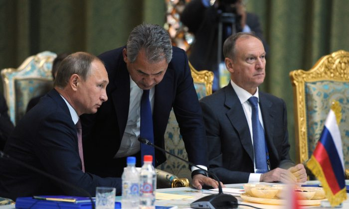 Russian President Vladimir Putin listens to Russia's Defense Minister Sergei Shoigu (C) at the meeting of the Collective Security Treaty Organization (CSTO) in Dushanbe, Tajikistan, on Sept. 15, 2015. (Mikhail Klimentyev/RIA-Novosti via AP)