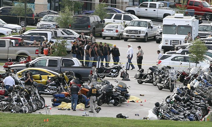 FILE - In this May 17, 2015 file photo, authorities investigate a shooting in the parking lot of the Twin Peaks restaurant, in Waco, Texas. Bikers and public watchdogs have criticized authorities here for how they've handled the shooting investigation, citing the mass arrests of more than 170 people held for days or weeks on $1 million bonds without sufficient evidence to support those arrests four months after the shootings.  (AP Photo/Jerry Larson, File)