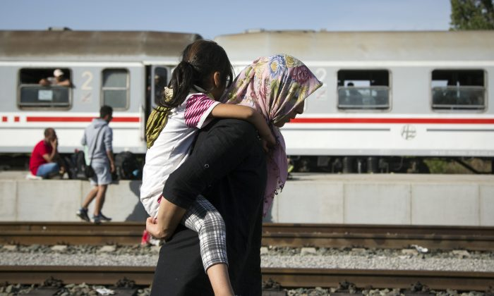 A refugee woman carries a child at a train station in Beli Manastir, near Hungarian border, northeast Croatia, early Friday, Sept. 18, 2015. Croatian police say some 13,300 migrants have entered the country from Serbia since the first groups started arriving more than two days ago. (AP Photo/Darko Bandic)