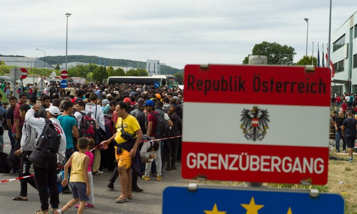 Migrants queue up for buses after they arrived at the border between Austria and Hungary near Heiligenkreuz, about 180 kms (110 miles) south of Vienna, Austria, Saturday, Sept. 19, 2015. (AP Photo/Christian Bruna)