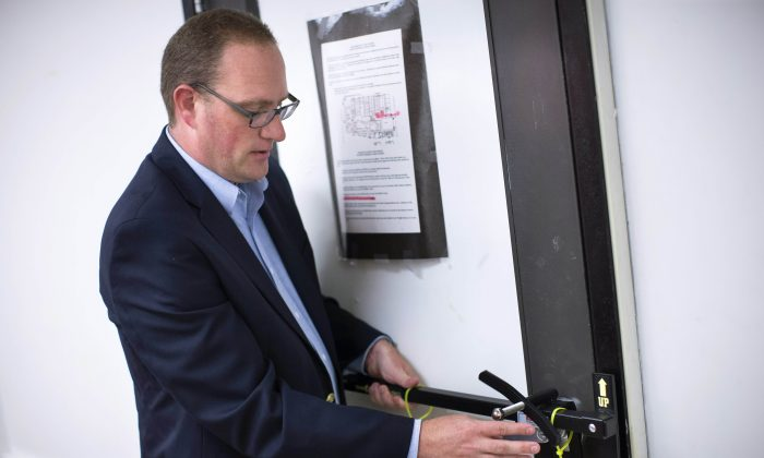 In this Monday, July 20, 2015 file photo, Ben Richards, principal of Watkins Memorial High School, demonstrates the use of an ALICE, or Alert Lockdown Inform Counter Evade, device in Pataskala, Ohio. (AP Photo/John Minchillo)
