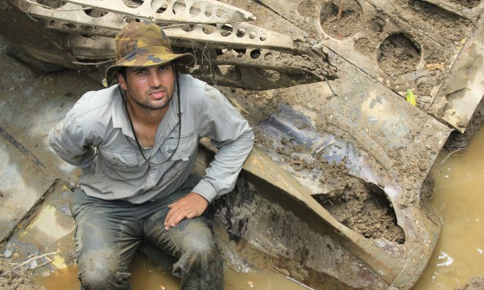 In this 2014 photo provided by Pacific Wrecks, Justin Taylan, founder and director of Pacific Wrecks poses at a World War II airplane wreck site in Papua New Guinea (PNG). (Marcus Browning/Pacific Wrecks via AP)