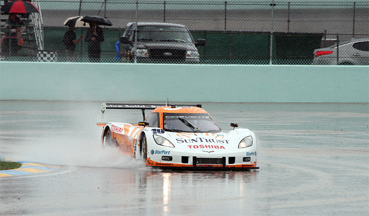 The No. 10 SunTrust Dallara-Corvette kicks up a wave as it passes through puddles on Homestead-Miami Speedway during the Rolex Grand Prix of Miami. (Chris Jasurek/The Epoch Times)