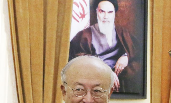 """FILE - In this July 2, 2015 file photo, U.N. nuclear chief Yukiya Amano stands as Secretary of Iran's Supreme National Security Council Ali Shamkhani shakes hands with delegation members before the start of their meeting in Tehran, Iran. Iran's state TV is reporting Amano has arrived in Tehran, to """"clarify past and current issues"""" of the country's nuclear program. Iran and the world powers have agreed to a landmark deal that curbs Iran's nuclear program in return for the lifting of international economic sanctions. (AP Photo/Vahid Salemi, File)"""