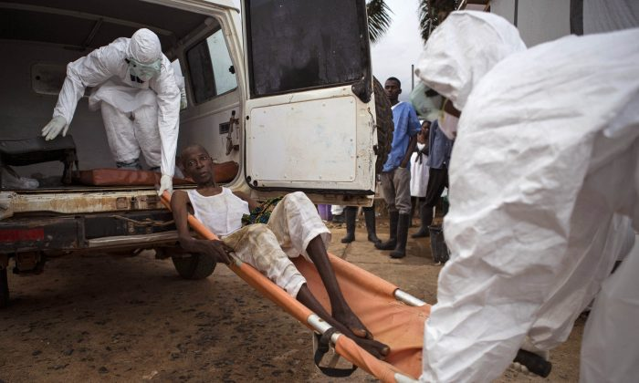 Healthcare workers carry a man suspected of suffering from the Ebola virus into an ambulance in Kenema, eastern Sierra Leone, on Sept. 24, 2014. (AP Photo/Tanya Bindra)