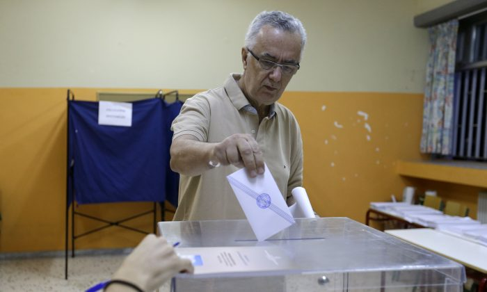 A man casts his vote at a polling station in Athens, Sunday, Sept. 20, 2015.  (AP Photo/Thanassis Stavrakis)