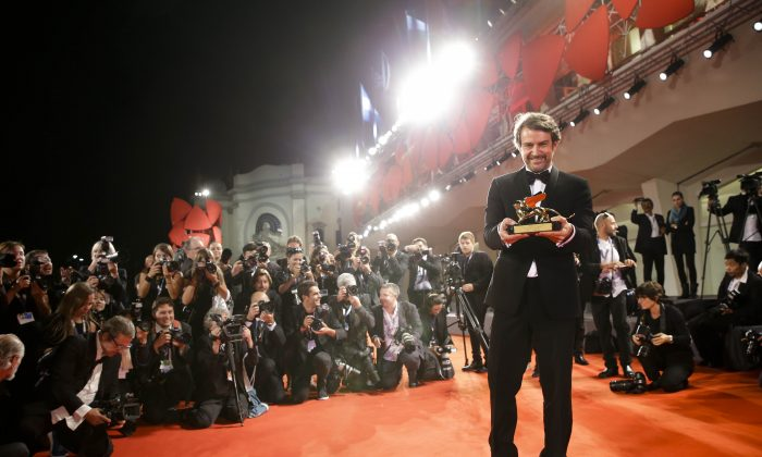 Director Lorenzo Vigas poses with the Golden Lion for best film for 'Desde Alla' (From afar) on the red carpet at the end of the awards ceremony of the 72nd edition of the Venice Film Festival in Venice, Italy, Saturday, Sept. 12, 2015. (AP Photo/Andrew Medichini)