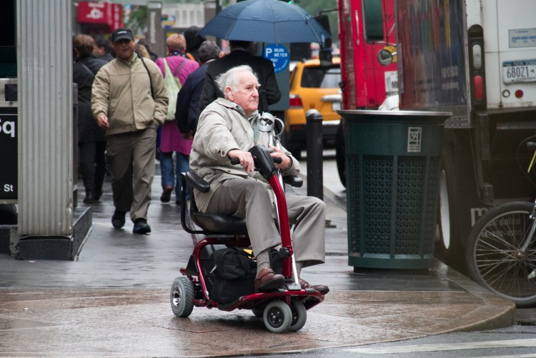 An elderly man drives a motorized wheelchair across the busy intersection of Sixth Avenue and 34th Street in Manhattan on April 26.