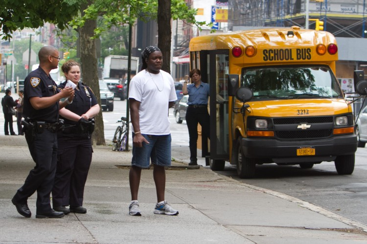 The custodian at the Meyer London PS 2 who was shot with a BB gun, waits next to police officers for an ambulance to come and examine him on May 23. (Benjamin Chasteen/The Epoch Times)