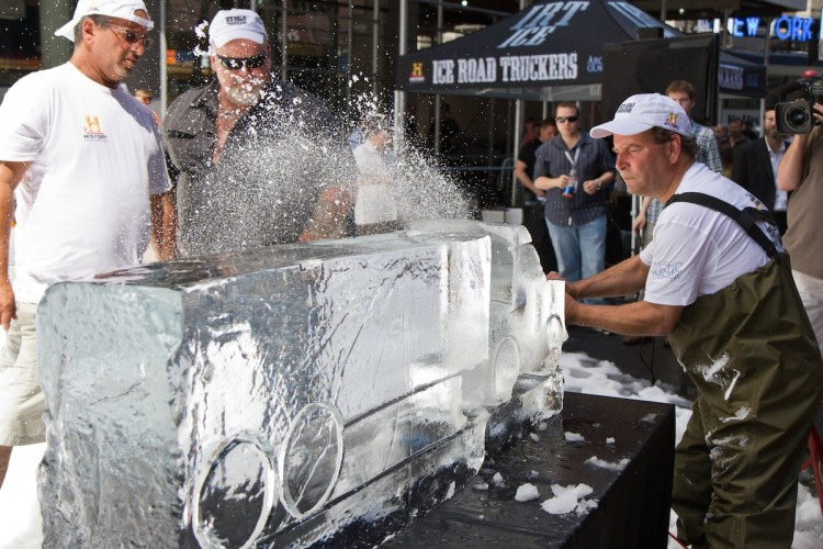 """An ice sculptor creates a truck in a block of ice using a chainsaw in 80 degree weather right in the heart of Times Square Thursday. The demonstration was a marketing campaign for History Channel's """"Ice Road Truckers."""" Star of the show, Hugh """"Polar Bear"""" Rowland, looks on. (Benjamin Chasteen/The Epoch Times)"""