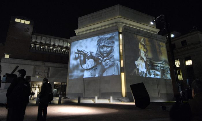 FILE - In this Monday, Nov. 20, 2006, file photo, images from Darfur and Chad are projected on the exterior walls of the United States Holocaust Memorial Museum in Washington. To try to predict and prevent mass killings, the museum is making both sophisticated statistical analysis and feedback from experts publicly available for the first time to produce early warnings that can help governments, policy makers, advocacy groups and scholars decide where to concentrate their efforts. The Early Warning Project online tool was announced Monday, Sept. 21, 2015. (AP Photo/Nick Wass)