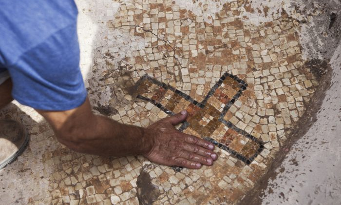 A worker for the Israel Antiquities Authority shows a cross designed on a mosaic floor at an archaeological site at Ben Shemen Forest near the Israeli city of Modiin on Monday, Sept. 21, 2015. Amit Reem, an Israeli archaeologist for the Israel Antiquities Authority, said the cross is a clue. It appears on the floor of a burial niche at the site. It is the only Byzantine-era site where a cross decorates the floor of a burial vault, he said, indicating that it may have marked the spot of an important figure. (AP Photo/Dan Balilty)