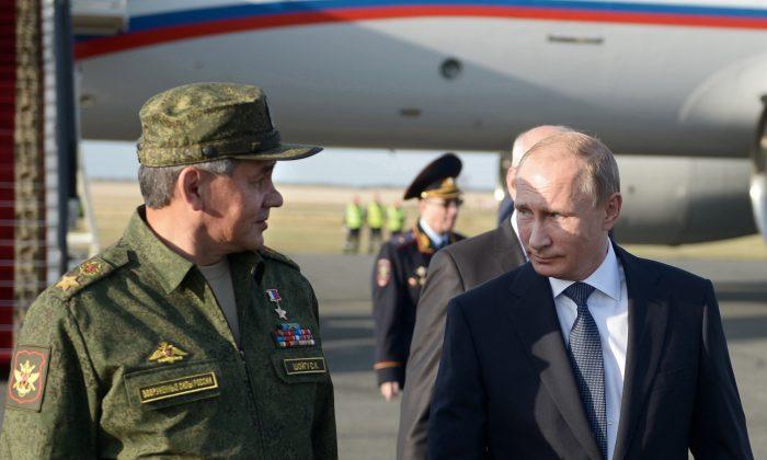 Russian President Vladimir Putin speaks with Defense Minister Sergei Shoigu on his arrival in Orenburg region, about 800 miles southeast of Moscow, Russia, on Sept. 19, 2015. (Alexei Nikolsky/RIA-Novosti via AP)