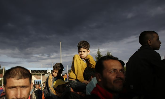 Refugees line up to cross the border from Croatia to the Slovenian village Rigonce at the border station in Harmica, Croatia, Sunday, Sept. 20, 2015. (AP Photo/Markus Schreiber)