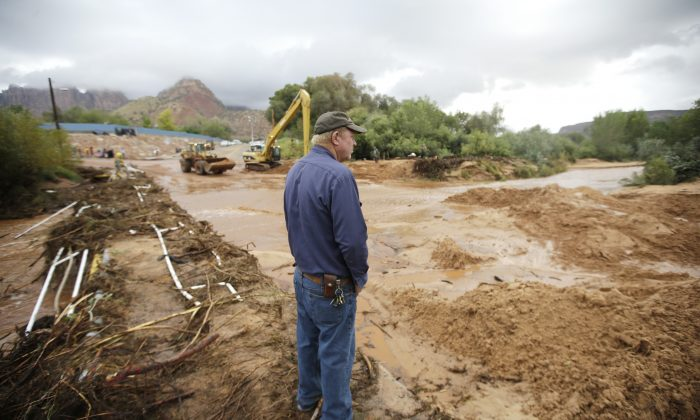 A man looks on as crews clear mud and debris from a road following a flash flood Tuesday, Sept. 15, 2015, in Colorado City, Ariz. (AP Photo/Rick Bowmer)