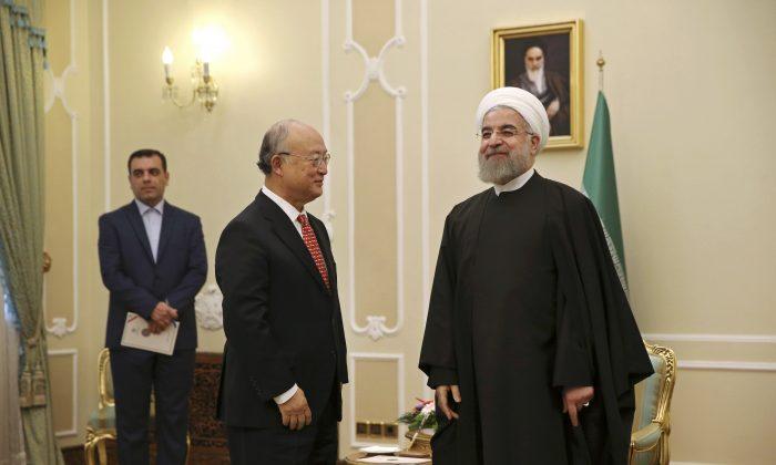 Iranian President Hassan Rouhani, right, welcomes U.N. nuclear chief Yukiya Amano for their meeting in Tehran, Iran, Sunday, Sept. 20, 2015. (AP Photo/Vahid Salemi)