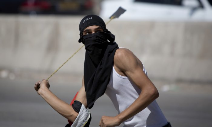 In this Friday, Sept. 18, 2015 file photo, a Palestinian uses a sling shot with stones during clashes with Israeli troops at Qalandia checkpoint between Jerusalem and the West Bank city of Ramallah. Israel is struggling with the resurgence of a weapon dating back to David and Goliath: the hurled rock. (AP Photo/Majdi Mohammed)
