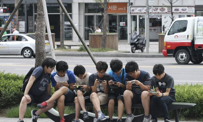 In this July 16, 2015, file photo, South Korean high school students play games on their smartphones on a bench on the sidewalk in Seoul, South Korea. (AP Photo/Ahn Young-joon)