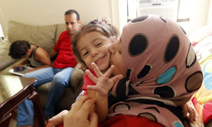 Maaesa Alroustom, center, is kissed by her mother, Suha, as her father, Hussam, back, sits with her brother Wesam in their apartment in Jersey City, N.J., Wed, Sept. 16, 2015. (AP Photo/Julio Cortez)
