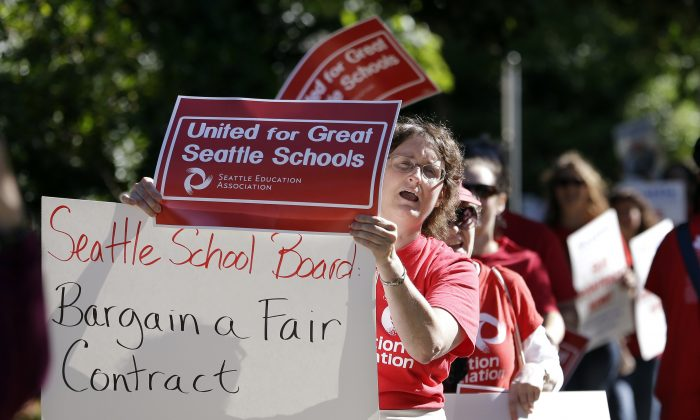 In this Sept. 2, 2015, file photo, dozens of teachers picket and chant as they march outside West Seattle High School in Seattle. (AP Photo/Elaine Thompson)