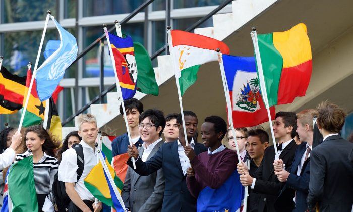 School children hold the flags of nations during the Peace Bell Ceremony to commemorate the International Day of Peace September 21, 2015 at the United Nations in New York. AFP PHOTO/DON EMMERT        (Photo credit should read DON EMMERT/AFP/Getty Images)