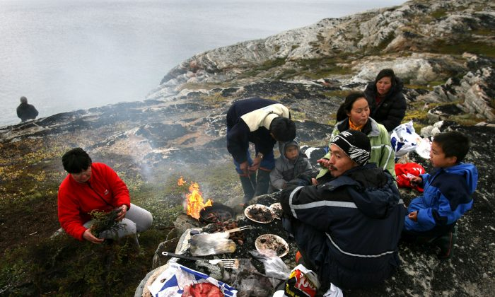 Arne Lange, a 39-year-old Inuit fisherman and his family have a family seal meat barbecue. (Photo by Uriel Sinai/Getty Images)