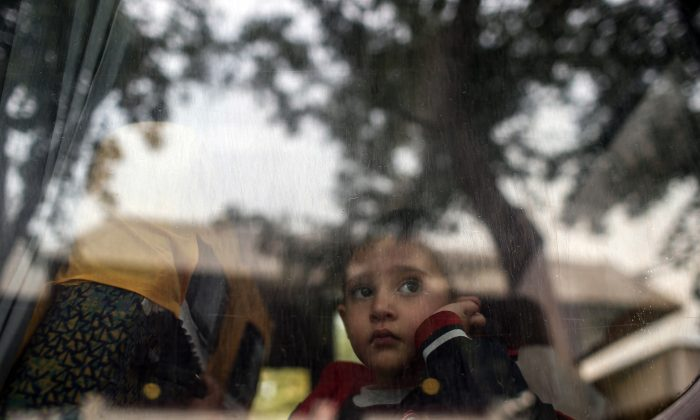 A refugee child looks through a bus window as they leave for Istanbul, abandoning plans to cross to Europe near Turkey's western border with Greece and Bulgaria, in Edirne, Turkey, Wednesday, Sept. 23, 2015. (AP Photo/Emrah Gurel)