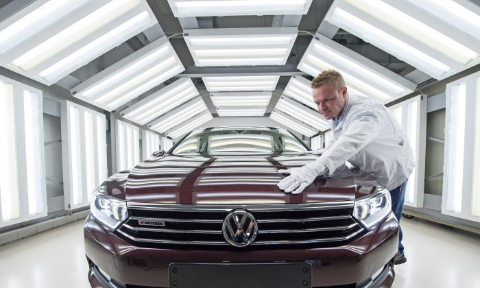 In this Jan 26, 2015 file photo worker Maik Neubert checks a Passat Variant car during the visual inspection during a press tour at the plant of the German manufacturer Volkswagen Sachsen in Zwickau, Germany. (AP Photo/Jens Meyer)
