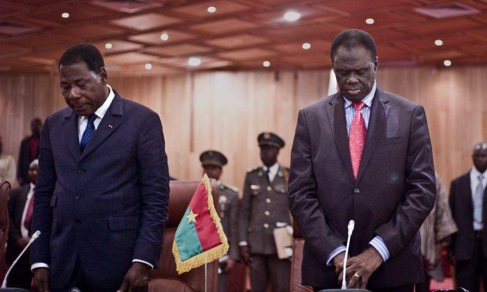 Burkina Faso's transitional president Michel Kafando (R) stands alonsgide Benin President Thomas Boni Yayi (L) during a official handover ceremony in Ouagadougou, Burkina Faso, Wednesday, Sept. 23, 2015. (AP Photo)