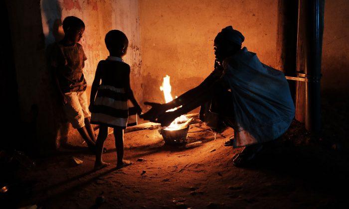 A homeless family cooks their dinner on an open fire in the street of Bujumbura, Burundi, on June 28, 2015. (Spencer Platt/Getty Images)
