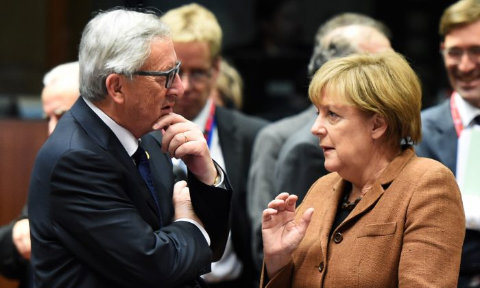 German federal chancellor Angela Merkel (R), speaks with European commmission's president Jean-Claude Juncker (L) prior to a round table as part of an extraordinary summit on migrants crisis, on September 23, 2015 at the UE headquarters in Brussels. (ALAIN JOCARD/AFP/Getty Images)