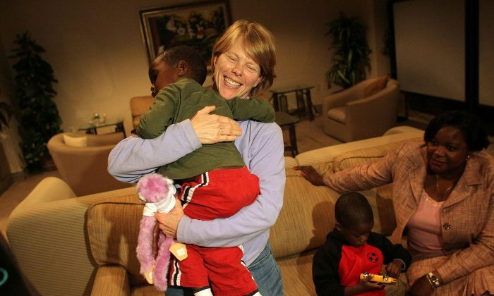 A foster mother holds her adoptive son in Miami, Fla., on Feb. 1, 2010. (Photo: Joe Raedle/Getty Images)