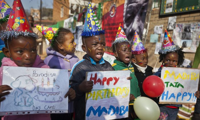 A group of kindergarten children singing Happy Birthday to Nelson Mandela outside the Mediclinic Heart Hospital in Pretoria, South Africa on July 18, 2013. (AP Photo/Ben Curtis, File)