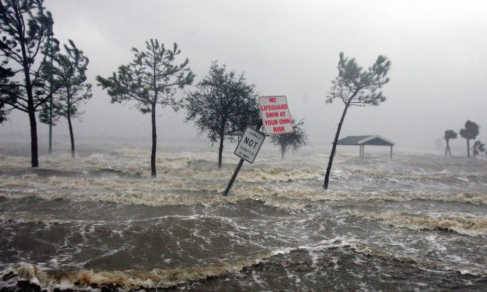Swirling floodwaters of Lake Charles lap onto the shore in the port city of Lake Charles, La., following landfall of Hurricane Rita in this Sept. 24, 2005 file photo. (AP (Photo/Ric Feld, File)