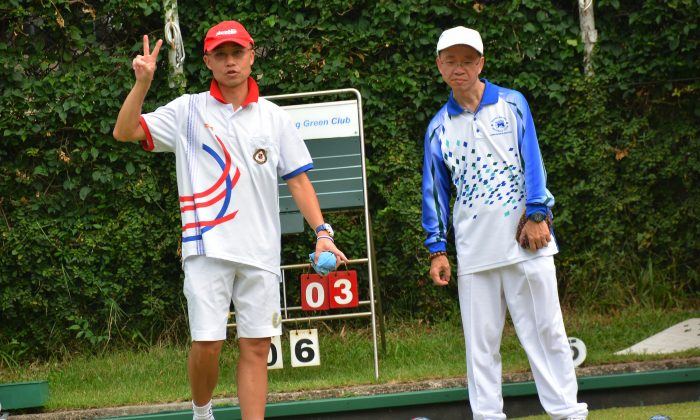 VICTORY!! Hong Kong international Stanley Lai (left) showed his Kowloon Bowling Green Club teammate the number of shots they are holding during his league match against Wagner Chan of Hong Kong Football Club on Sept 19, 2015. Lai emerged victorious by a big margin of 25:6. (Mike Worth)