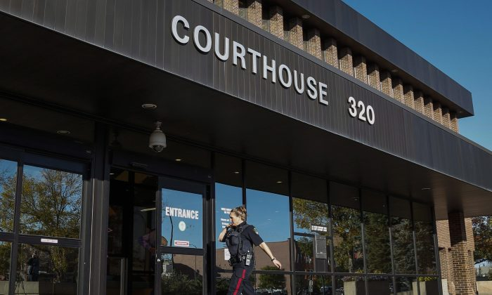 A police officer arrives at the provincial court building in Lethbridge, Alta., for the first court appearance of Derek James Saretzky, who is charged with two counts of first-degree murder in the deaths of Terry Blanchette and his two-year-old daughter Hailey Dunbar-Blanchette. (The Canadian Press/Jeff McIntosh)