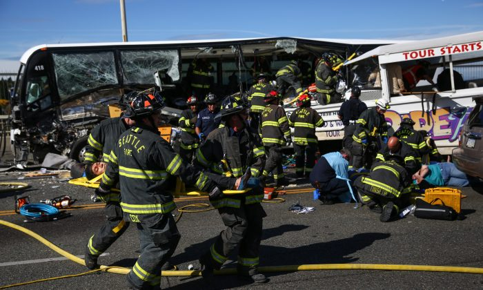 "Emergency personnel work at the scene of a fatal collision involving a charter bus, background, and a ""Ride the Ducks"" amphibious tour bus, right, on the Aurora Bridge in Seattle on Thursday, Sept. 24, 2015. (Joshua Trujillo/seattlepi.com via AP)  NO SALES; MAGS OUT; SEATTLE OUT; SEATTLE ONLINE OUT; SEATTLE TV ONLINE OUT; SEATTLE RADIO ONLINE OUT; SEATTLE TIMES OUT; KING OUT; KOMO OUT; KIRO TV OUT; KIRO RADIO OUT; MANDATORY CREDIT: JOSHUA TRUJILLO/SEATTLEPI.COM"