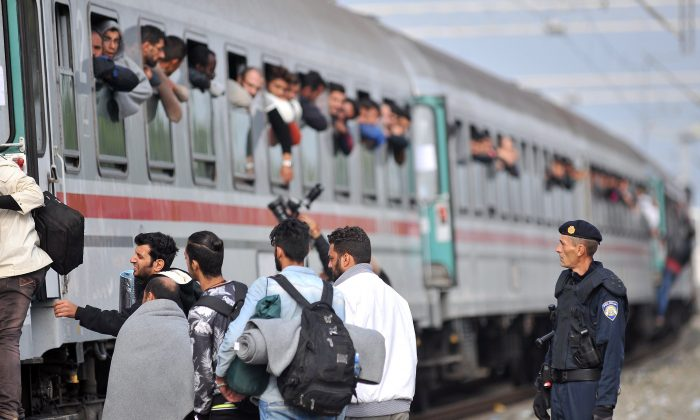 A Croatian police officer looks on as migrants and asylum seekers board a train at the train station in the eastern Croatian village of Tovarnik, near the official border crossing between Serbia and Croatia, on September 24, 2015. (ELVIS BARUKCIC/AFP/Getty Images)