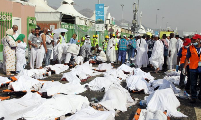 Saudi emergency personnel stand near bodies of Hajj pilgrims at the site where at least 717 were killed and hundreds wounded in a stampede in Mina, near the holy city of Mecca, at the annual hajj in Saudi Arabia on September 24, 2015. (STR/AFP/Getty Images)