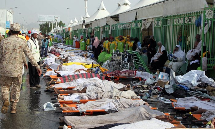 Saudi emergency personnel stand near bodies of Hajj pilgrims at the site where at least 717 were killed and hundreds wounded in a stampede in Mina, near the holy city of Mecca, at the annual hajj in Saudi Arabia on Sept 24. (STR/AFP/Getty Images)