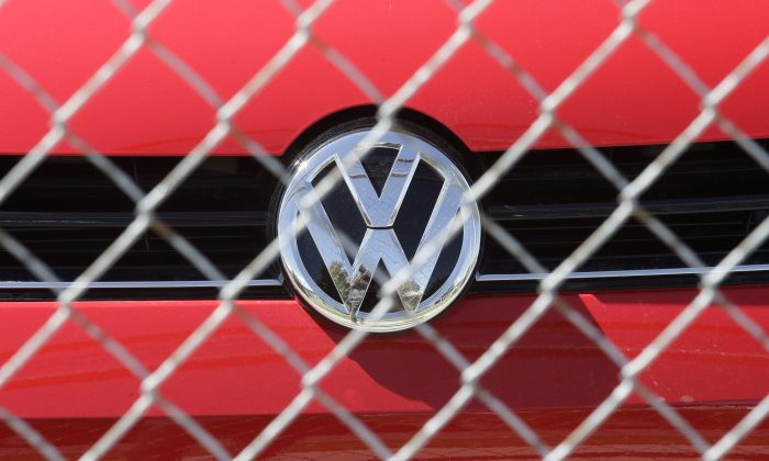 A Volkswagen diesel sits behind a security fence on a storage lot near a VW dealership in Salt Lake City, on Sept. 23, 2015. (Rick Bowmer/AP Photo)