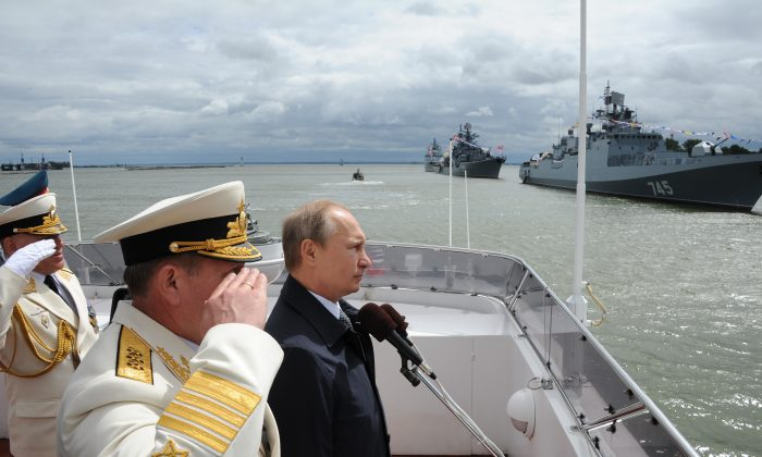 FILE - In this Sunday, July  26, 2015 file pool photo, Russian President Vladimir Putin, centre, reviews a Navy parade in Baltisk, western Russia, during celebration for Russian Navy Day. With dozens of Russian combat jets and helicopter gunships lined up at an air base in Syria, Russian President Vladimir Putin is ready for a big-time show at the United Nations General Assembly. Observers expect the Russian leader to call for stronger U.N.-sanctioned global action against the Islamic State group and possibly announce some military moves in his speech on Monday, Sept. 28, 2015. (Mikhail Klimentyev/RIA-Novosti, Kremlin Pool Photo via AP, file)