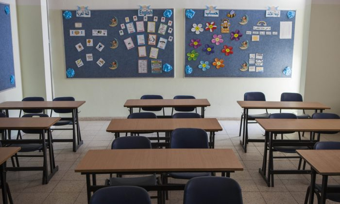 In this photo taken Tuesday, Sept. 22, 2015, an empty classroom is seen at a Christian cchool In the central Israeli city of Ramle. The Israeli school year has begun, but thousands of children from the Arab minority who attend Christian schools are still on summer vacation because of a strike to protest cuts in government funding that critics say amount to discrimination. (AP Photo/Dan Balilty)