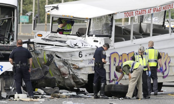 Seattle Police investigators examine the front tire from a Ride the Ducks tour bus as it lies on the ground following a crash involving the tour bus and several other vehicles, Thursday, Sept. 24, 2015 in Seattle. (AP Photo/Ted S. Warren)