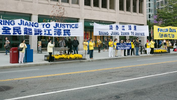 "Falun Gong practitioners hold a banner saying ""Prosecute Jiang Zemin,"" on the streets of Washington, D.C. on Sept. 24. (Lisa Fan/Epoch Times)"